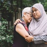 A young woman hugging an older woman, helping her cope with the loss of a loved one